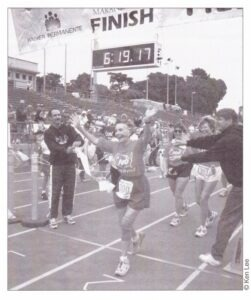 Photo of an older woman runner crossing a marathon finish line