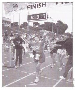 Photo of an older woman runner crossing a marathon finish line